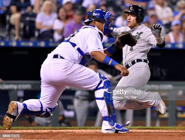 Detroit Tigers' Jose Iglesias scores before the ball reaches Kansas City Royals catcher Salvador Perez on a tworun single by Miguel Cabrera in the...