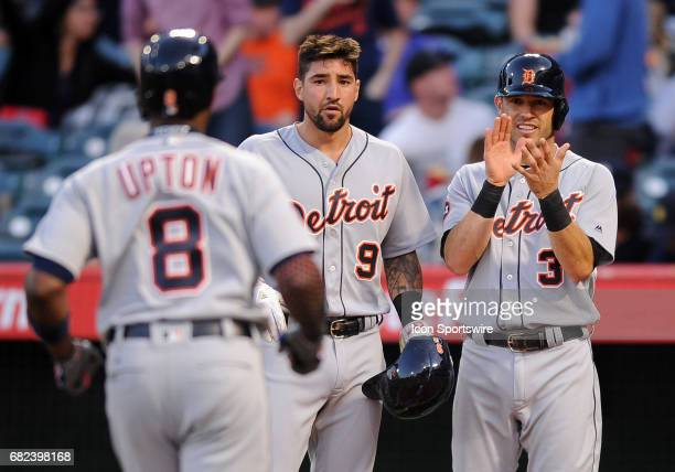 Detroit Tigers Nicholas Castellanos and Ian Kinsler waiting at home plate for teammate Justin Upton after Upton hit a three run home run in the first...
