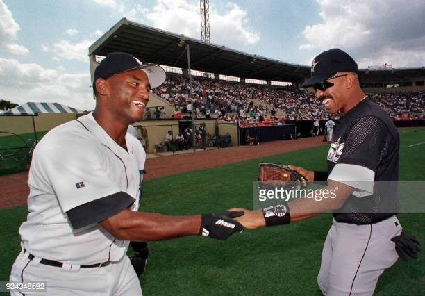 Detroit Tigers outfielder Curtis Pride and Houston Astros player Derek Bell greet each other on the infield before their spring training game at...