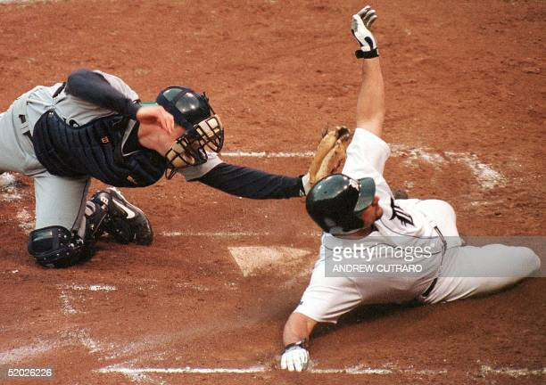 Detroit Tigers' right fielder Bobby Higginson slides into home plate while being tagged out by Seatle Mariners' catcher Dan Wilson during the fifth...