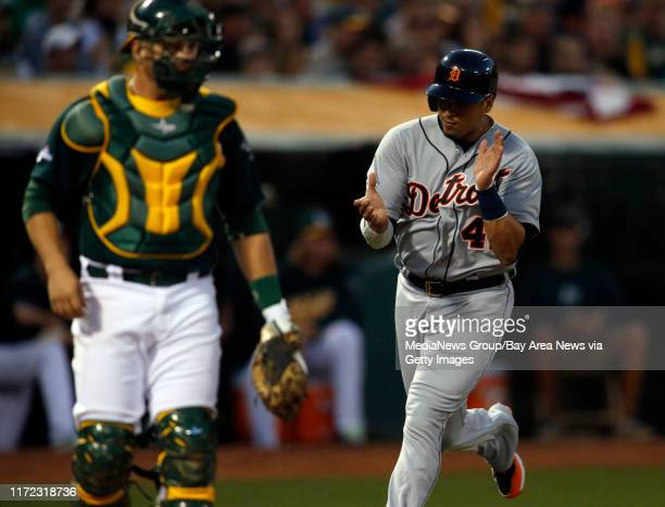 Detroit Tigers' Victor Martinez scores in the first inning Game 1 of the American League Division Series running past Oakland Athletics' catcher...