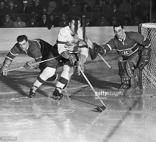 Detroit's Alex Delvecchio has the puck at the end of his stick as he tries to push it past Montreal goalie Jacques Plante during the third period of...