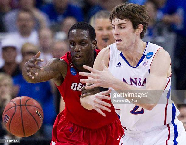 Detroit's Jason Calliste left and Kansas' Conner Teahan chase a loose ball in the first half of NCAA Tournament secondround action at the CenturyLink...