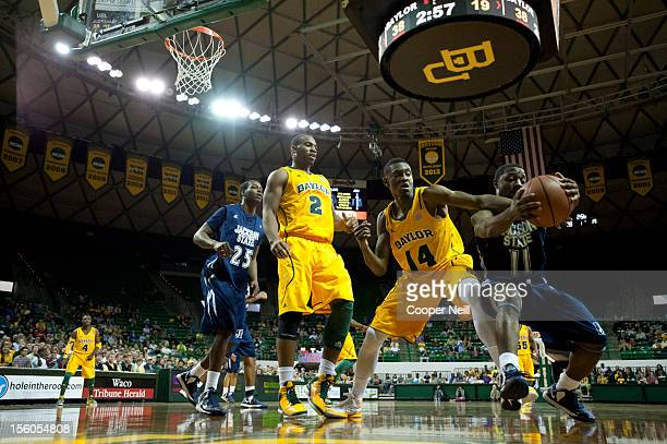 Deuce Bello of the Baylor University Bears and Keeslee Stewart of the Jackson State University Tigers fight for the ball on November 11 2012 at the...
