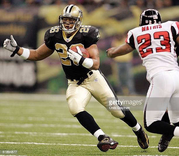 Deuce McAllister of the New Orleans Saints avoids a tackle by Kevin Mathis of the Atlanta Falcons at the Louisiana Superdome December 26 2004 in New...