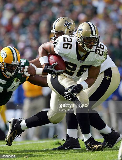 Deuce McAllister of the New Orleans Saints runs with the ball past Roy Manning of the Green Bay Packers during the first quarter at Lambeau Field on...
