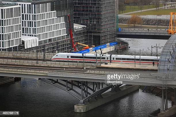 A Deutsche Bahn AG InterCity Express train leaves Berlin Central Station as construction cranes stand outside beside a commercial building site on...