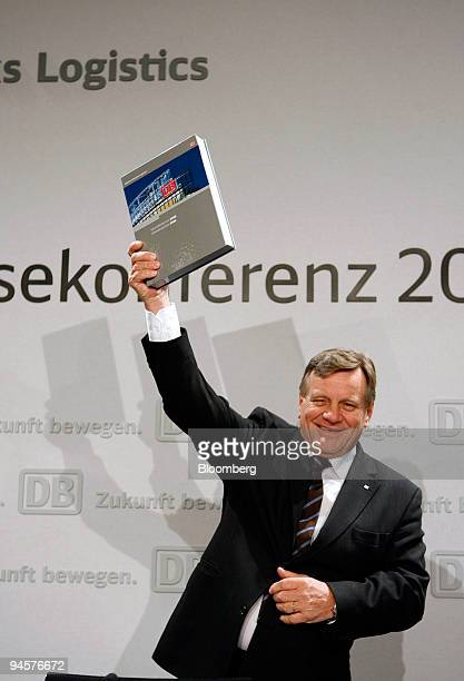 Deutsche Bahn Chief Executive Officer Hartmut Mehdorn shows the company's annual earnings report while arriving for a press conference in Berlin...