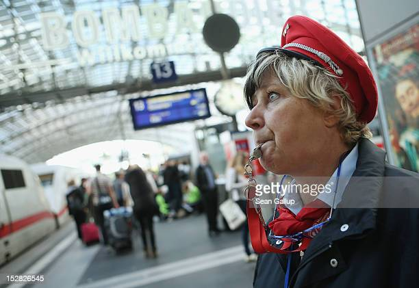 Deutsche Bahn employee blows a whistle to signal that a train is ready for departure at Hauptbahnhof main railway station on September 27 2012 in...
