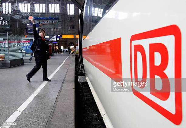 Deutsche Bahn employee signals that an ICE or InterCity Express train is ready for departure at the main train station in Leipzig Germany on Thursday...