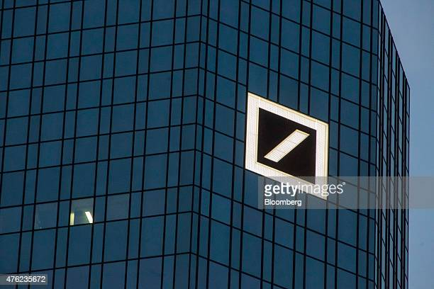 A Deutsche Bank logo sits on display on the twin tower skyscraper headquarters of Deutsche Bank AG at dusk in Frankfurt Germany on Saturday June 6...