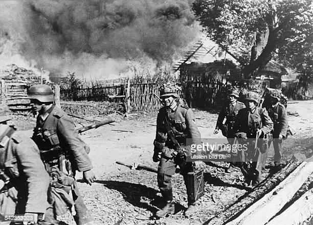 Deutsche Infanteristen ziehen durchein brennendes DorfAnfang August 1941