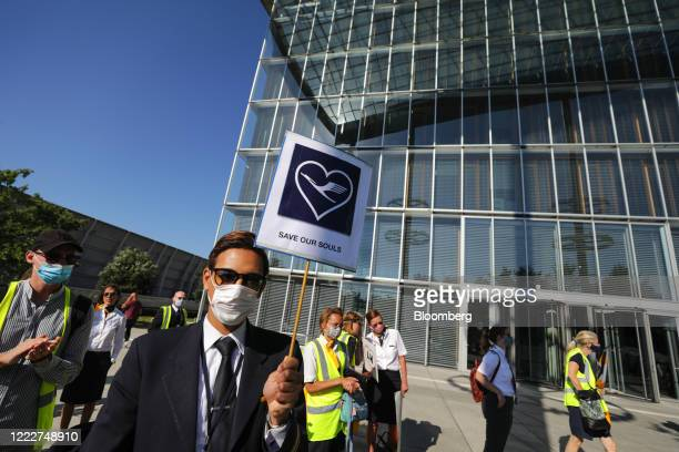 A Deutsche Lufthansa AG employee wearing a protective face mask holds a banner as employees and union members gather for a protest outside the...