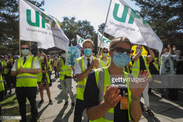 Deutsche Lufthansa AG employees and Unabhaengige Flugbegleiter Organisation employment union members wear protective face masks and wave flags as...