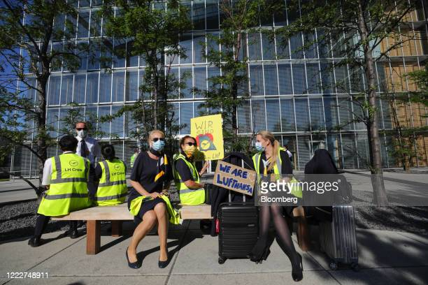 Deutsche Lufthansa AG employees wear protective face masks as they sit with luggage during a protest outside the Lufthansa Aviation Center at...