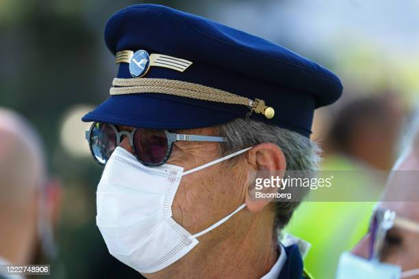 A Deutsche Lufthansa AG pilot wears a protective face masks as employees and union members gather for a protest outside the Lufthansa Aviation Center...