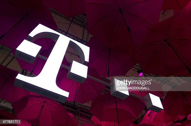 Deutsche Telekom T-Mobile logo hangs under pink umbrellas at the stand of the German telecommunications giant at the 2014 CeBIT computer technology...