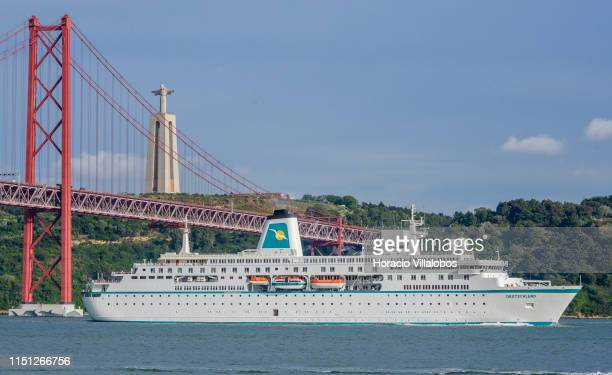 Deutschland a cruise ship registered in Nassau Bahamas sails past the 25 de Abril Bridge on the Tagus River while leaving harbor on her way to...