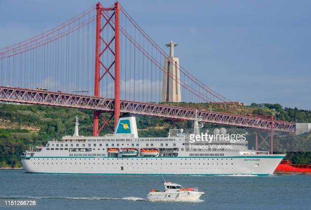 Deutschland a cruise ship registered in Nassau Bahamas sails the Tagus River under the 25 de Abril Bridge while leaving harbor on her way to Leixoes...