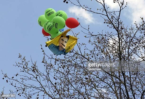 Deutschland Berlin 1 Mai in Kreuzberg Kurdische Fahne mit Portrait von Kurdenfuehrer Abdullah Öcalan und Luftballons in einer Baumkrone