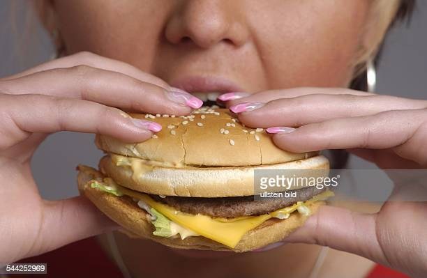 Deutschland, Berlin, - eine Frau isst einen Big Mac von McDonalds
