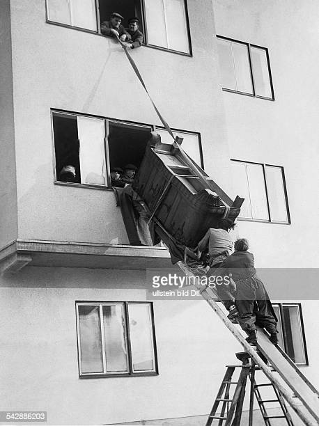 Deutschland Berlin Grosses Möbelstück wird durch das Fenster in die Neubauwohnung geschafft 1954