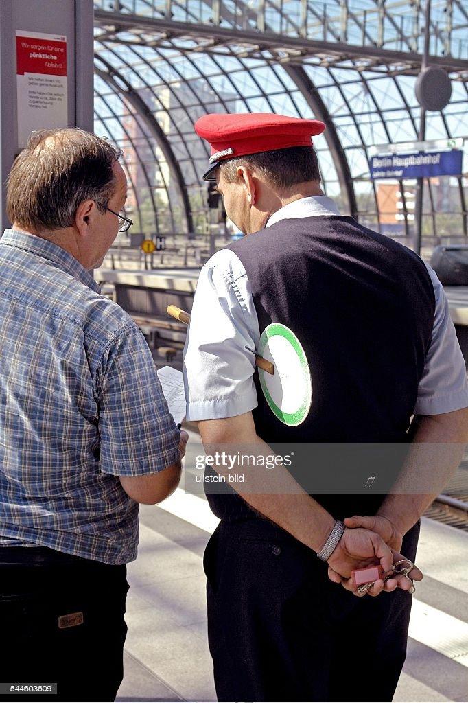 Deutschland, Berlin, Hauptbahnhof, Bahnreisender auf dem Berliner Hauptbahnhof informiert sich bei der Zugaufsicht : Foto jornalística