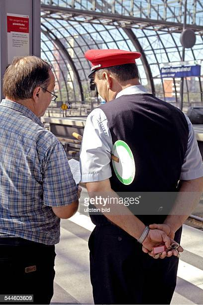 Deutschland, Berlin, Hauptbahnhof, Bahnreisender auf dem Berliner Hauptbahnhof informiert sich bei der Zugaufsicht