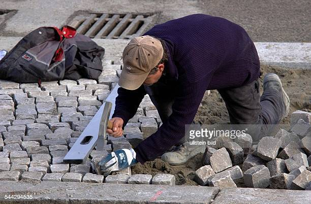 Deutschland, Berlin Mitte: ein Steinsetzer pflasterteinen Gehweg.- April 2006