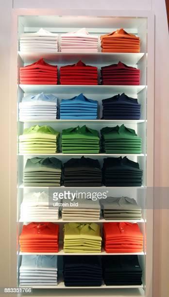 Deutschland Berlin Mitte Lacoste Shop in der Muenzstrasse Regal mit Polohemden in verschiedenen Farben
