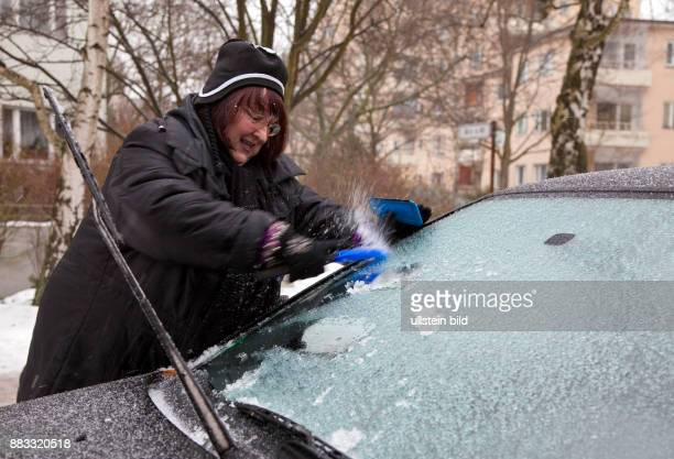 Deutschland Berlin rau mit einem Eiskratzer entfernt das Blitzeis von der Frontscheibe ihres Autos