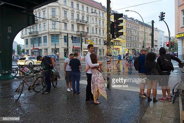 Deutschland, Berlin, U-Bahnhof Eberswalder Strasse , Warten an der Ampel, Paar in heller Kleidung, Regentag