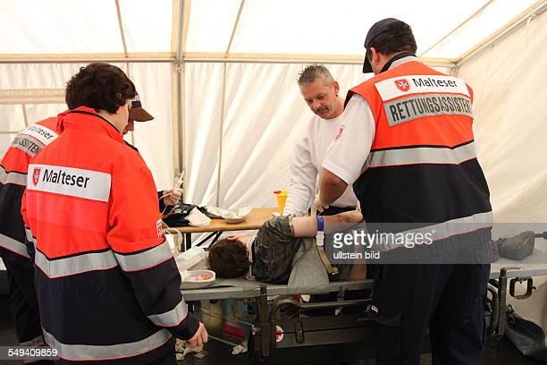 Deutschland. Dortmund: die Loveparade Waehrend die einen Feiern arbeiten die Malteser ehrenamtlich; Versorgung einer Person.