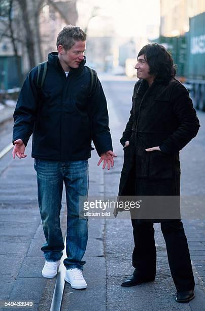 Freizeit Zwei junge Maenner unterwegs auf einer Strasse sie unterhalten sich l DEU Germany Free time Two young men walking in a street they are...