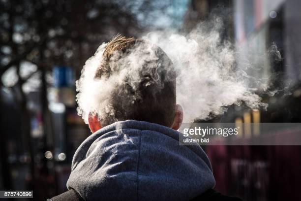 DEU Deutschland Germany Berlin Der Rauch einer EZigarette umhüllt den Kopf eines Mannes auf dem Kudamm