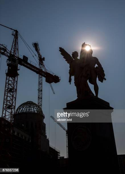 DEU Deutschland Germany Berlin Der Rohbau des Stadtschlosses im Gegenlicht mit Staturen auf dem Brücke