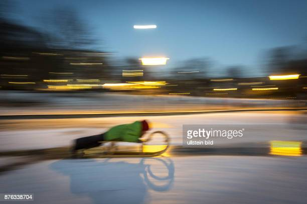 DEU Deutschland Germany Berlin Ein Junge rutscht mit seinem Schlitten über eine gefrorene Eisfläche im Weinbergspark in BerlinMitte