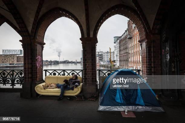 DEU Deutschland Germany Berlin Ein Obachloser sitzt neben seinem Zelt auf einem Sofa auf der Oberbaumbrücke zwischen Kreuzberg und Friedrichshain