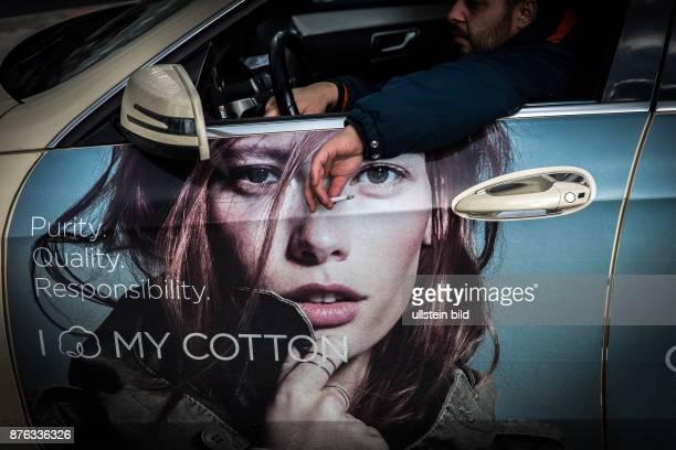 DEU Deutschland Germany Berlin Ein Taxifahrer hält seine brennende Zigarette aus dem offenen Autofenster auf dem ein Werbungbanner für eine Modefirma...