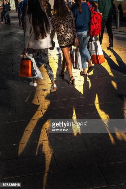 DEU Deutschland Germany Berlin Passanten werfen ihre Schatten auf Berlin populäre Einkaufsstrasse den Tauentzien Das Gold einer Glasfassade spiegelt...