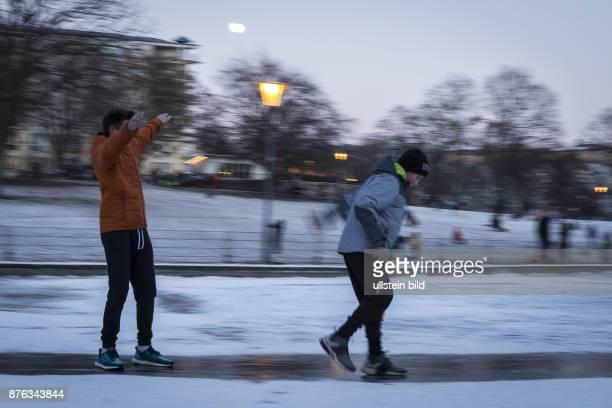 DEU Deutschland Germany Berlin Zwei Jugendliche rutschen über eine gefrorene Eisfläche im Weinbergspark in BerlinMitte