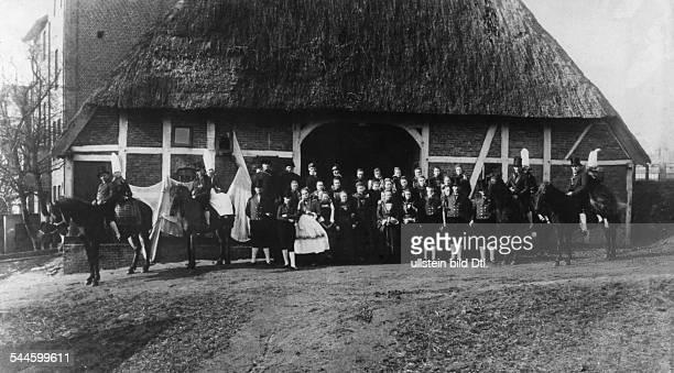 Deutschland Hamburg: Finkwarder Speeldeel in Finkenwerder Tracht vor einem Bauernhaus, auf den Pferden Hochzeitsbitter. - um 1910