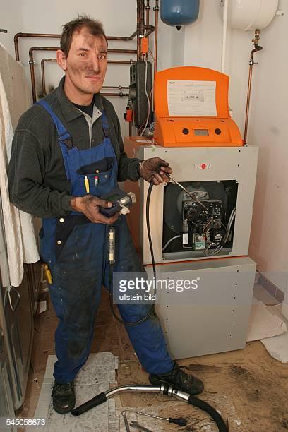 Deutschland Hessen Eschwege Handwerk Heizungstechniker bei der Reparatur des Brenners eines Heizkessels einer Ölheizung