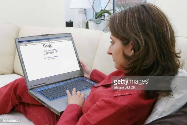 Deutschland Internethandel OnlineShopping Frau sitzt zuhause auf dem Sofa und surft mit Notebook im Internet auf der Seite der Suchmaschine Google