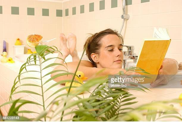 Deutschland Junge Frau entspannt sich in der Badewanne mit einem Buch vorhanden