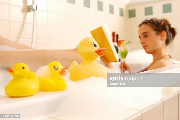 Deutschland Junge Frau entspannt sich in der Badewanne mit einem Buch und einem Cocktail vorhanden