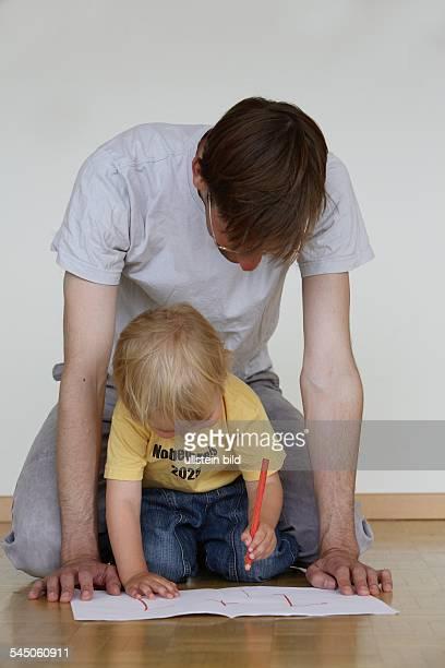Deutschland Kind mit TShirt mit der Aufschrift Nobelpreis 2025 uebt Rechnen mit dem Vater