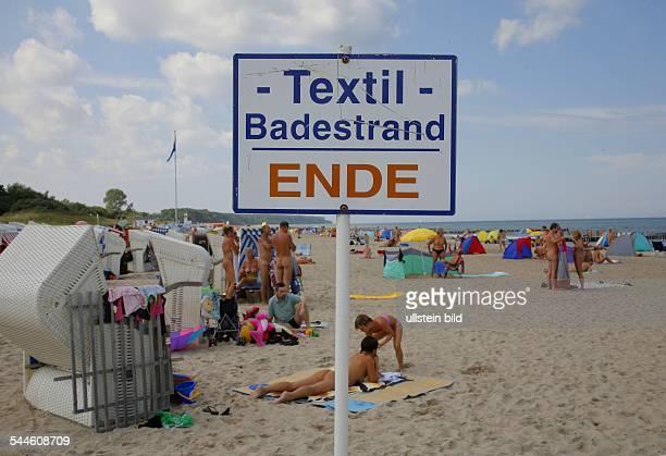 Deutschland MecklenburgVorpommern Badegaeste am Strand von RostockWarnemuende FKK Strand Schild TextilBadestrand Ende