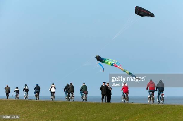 Deutschland Niedersachsen Cuxhaven Spaziergaenger Lenkdrachen und Radfahrer auf einem Deich an der Nordsee