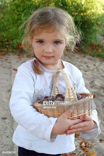 Deutschland NordrheinWestfalen Dortmund Sonniger Herbsttag auf dem Spielplatz Ein vierjähriges blondes Mädchen hält einen Korb mit gesammelten...